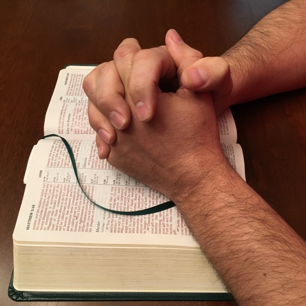 Hands resting on a Bible, folded in prayer